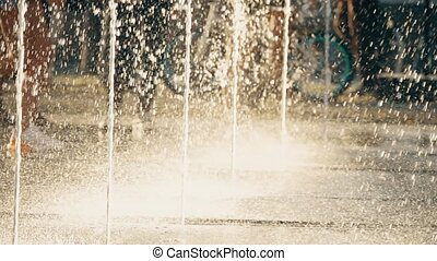 People in a city park and fountain streams, slow motion