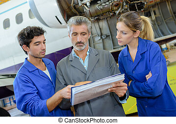 People in aircraft hangar looking at paperwork