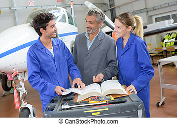 People in aircraft hangar looking in book