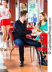 People in American diner or restaurant eating fast food