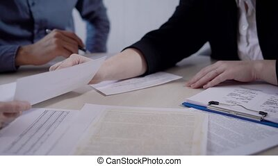 people in an office are discussing a conditions of contract,...