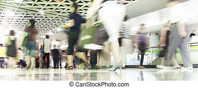 People in blurred motion in a subway station