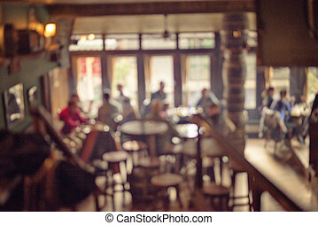 People in Coffee shop blur background with bokeh lights, vintage filter for old effect, blurred background. Image displays a pleasing paper grain and texture at 100 percent.