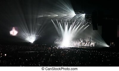 people in concert hall look at singer in light of beams