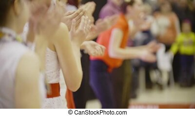 People in evening dresses at party applaud - clapping hands of people on dancing event - boogie-woogie, defocused