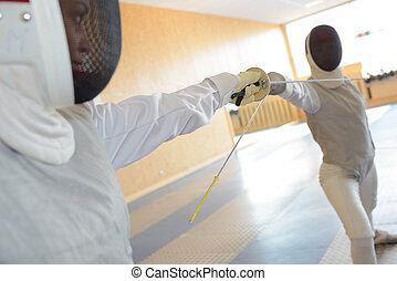People in fencing combat