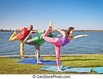 People in group  practice Yoga asana on lakeside.