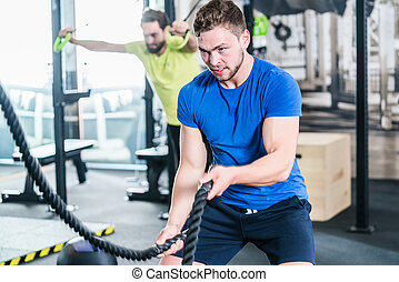 People in gym doing sport in functional fitness training