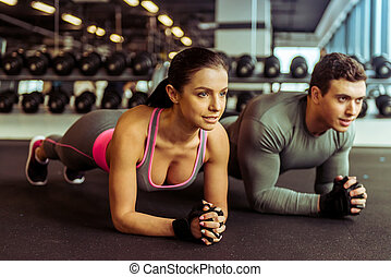 People in gym - Attractive young muscular man and woman...