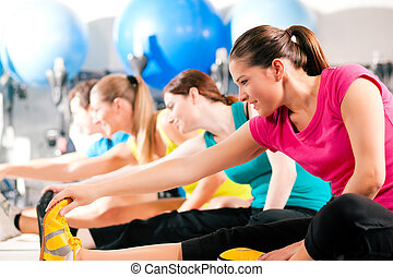 People in gym warming up stretching - Group of four people ...