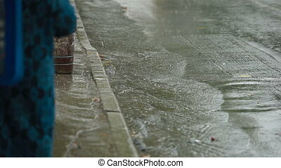 People in heavy rain on the sidewalk