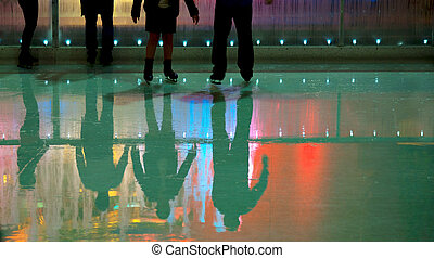 People in ice skating rink with mulii colored lights