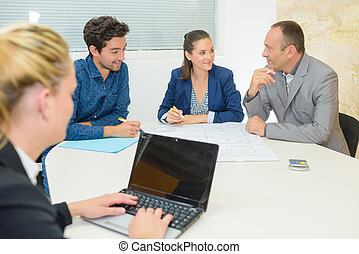 People in meeting, woman using computer