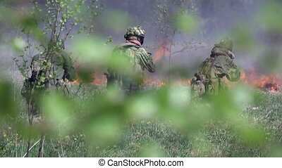 People in military uniform on background of fire after...