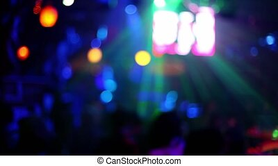 People in night club with colorful illumination and video screen, unfocused view