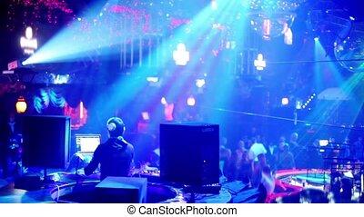 People in night club with illumination, dj on workplace