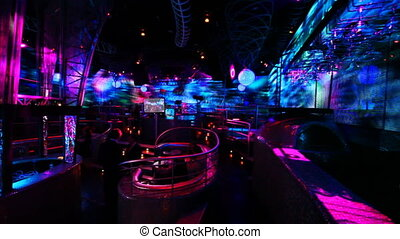 people in nightclub with bright LED illumination on walls