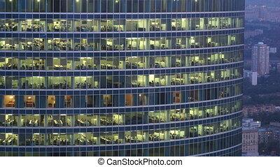 People in office-skyscraper windows do the work