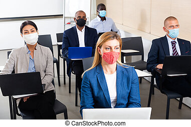 People in protective masks working with laptops during business training