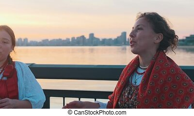 People in russian folk costumes standing on the waterfront during the sunset and singing a song