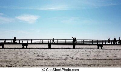 people in silhouette walking on walkway across beach