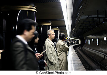 People waiting for a train in a Tokyo subway