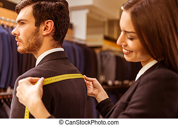 People in suit shop - Young beautiful female shop assistant ...