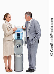 People in suit talking next to the water dispenser against...