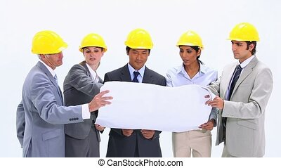 People in suits are looking at blueprints