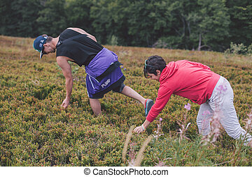 people in the mountains eating berries