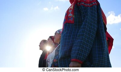 People in traditional folk clothes standing in a row on the field and singing a song