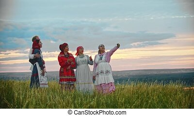 People in traditional folk clothes standing on the field and...