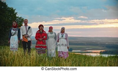 People in traditional folk clothes walking on the field and singing a song
