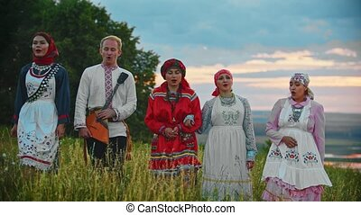 People in traditional folk clothes walking on the field and singing a song - sunset