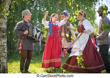People in traditional Russian clothes are dancing in the woods - one of them plays the accordion and singing - gorizontal view
