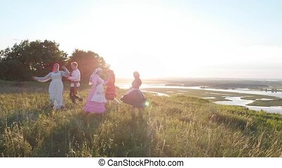 People in traditional Russian clothes are dancing on the...