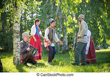 People in traditional Russian clothes are talking on the field and have fun - one of them plays the accordion and singing - gorizontal view