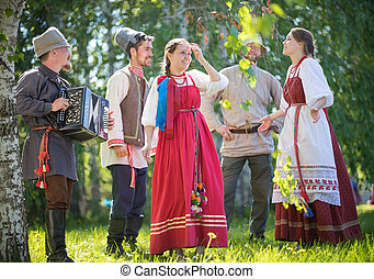 People in traditional Russian clothes communicate in the forest on the meadow - one of them plays music on accordion - gorizontal view