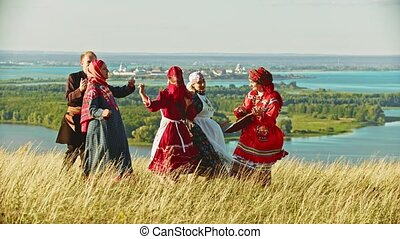 People in traditional russian clothes dancing on the field...