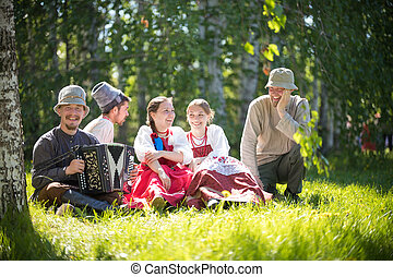 People in traditional Russian clothes sit on the lawn and talk - one of them plays the accordion and smile - gorizontal view