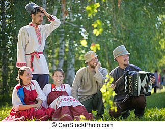 People in traditional Russian clothes sit on the lawn - one of them plays the accordion - gorizontal view