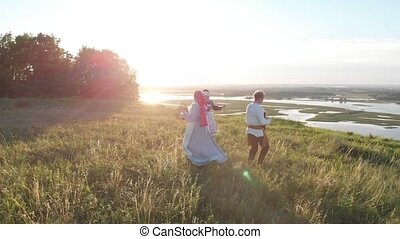 People in traditional Russian clothes standing in the grass...