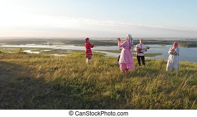 People in traditional Russian clothes take turns to the...