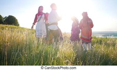People in traditional russian clothes walking in a circle and having fun - bright daylight
