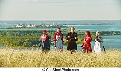 People in traditional russian clothes walking on the field...