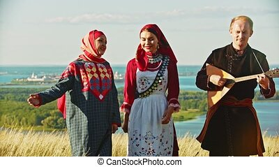 People in traditional russian clothes walking on the field and singing a song - a man playing balalaika