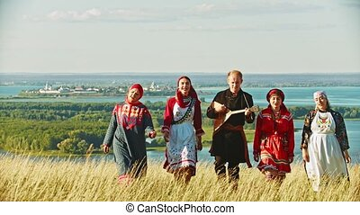 People in traditional russian clothes walking on the field and singing a song