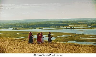 People in traditional russian clothes walking on the ray...