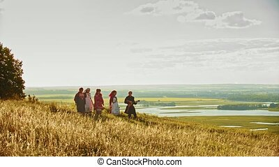 People in traditional russian clothes walking on the rye...