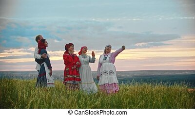 People in traditional russian folk clothes standing on the...